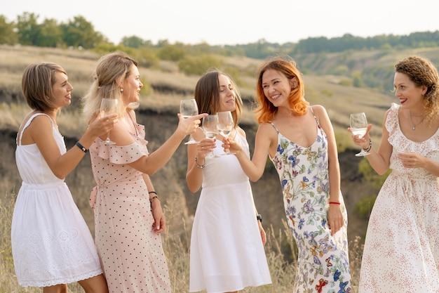 女性の友人の会社は夏のピクニックを楽しんで、ワインでグラスを上げる