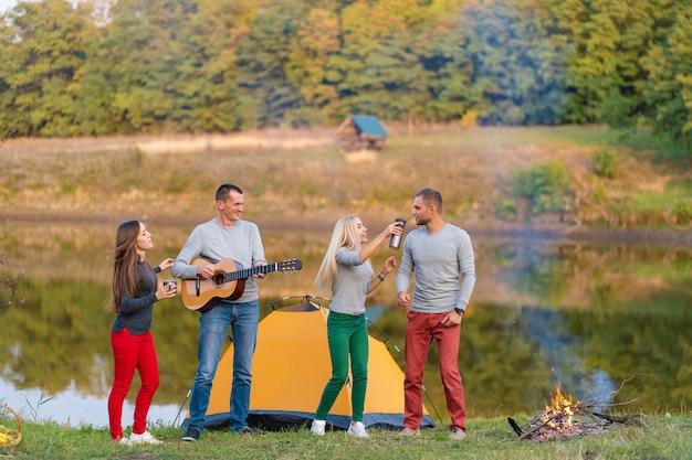 Группа счастливых друзей с гитарой, веселятся на открытом воздухе, танцуют и прыгают на берегу озера в парке фоне красивого неба. отдых на природе