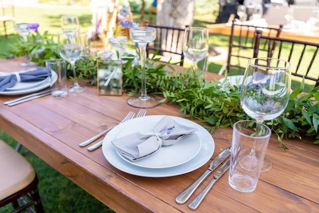 Красиво украшенный деревянный стол в летнем летнем кафе. зеленая ветвь и украшение стола свежими цветами