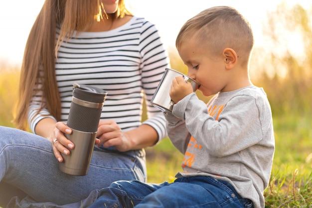 秋の散歩に幸せな家族。小さな息子を持つ若い美しい母親は、自然を楽しみます。