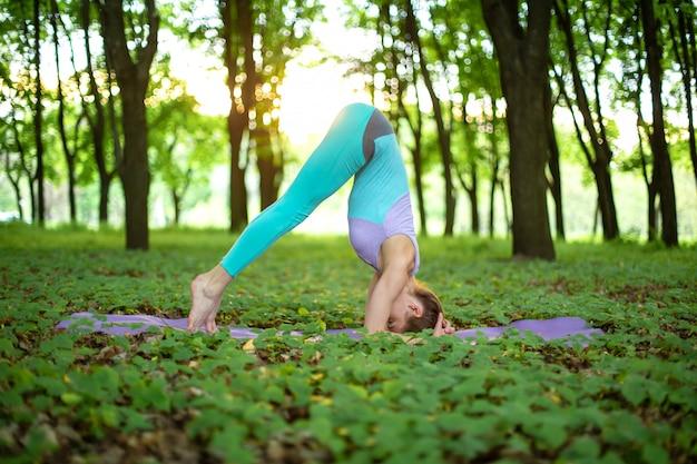 若いスポーツ少女は、やめられた緑の夏の森でヨガを練習します。瞑想と自然との一体化