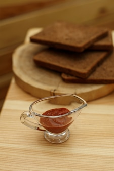 Стеклянный соусник с кетчупом на деревянном столе