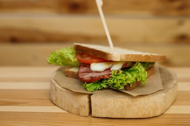 焼きパンとベーコンのジューシーなサンドイッチは、木製のプレートであなたを待っています