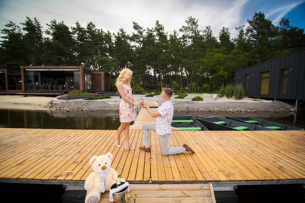 若いかわいい男は、木製の桟橋で彼の膝の上に立って、彼の最愛の女の子に結婚提案をします。木製の桟橋でのロマンスと愛
