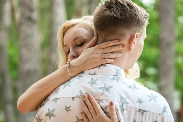 女の子と男は抱擁し、キスします。松林の中のロマンチックなデート、素敵なカップルのカップルが大好き