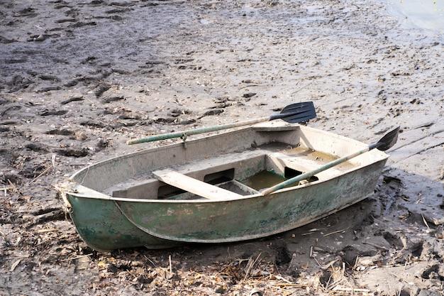 Металлическая лодка с веслами на берегу реки. рыболовный сезон