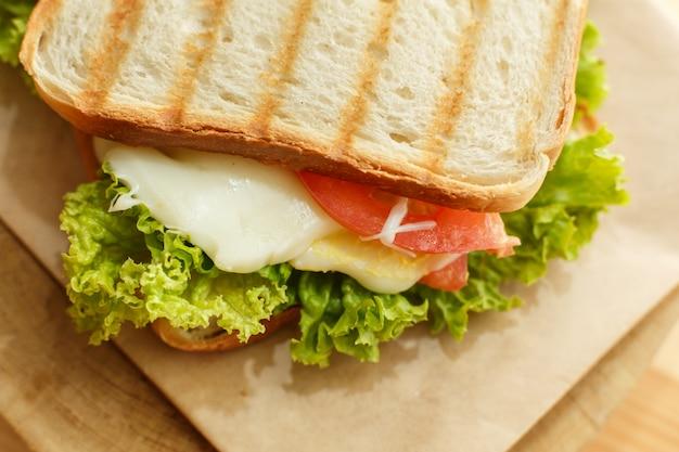 ベーコン、新鮮な野菜、グリーンサラダ、グリル後の暗いラインとジューシーなクローズアップサンドイッチ
