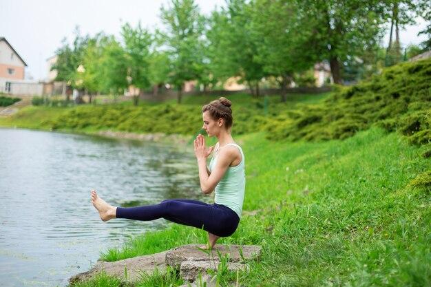 Молодая спортивная девушка занимается йогой на зеленой лужайке у реки, в позе йоги. медитация и единение с природой