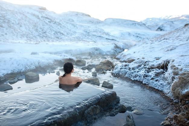女の子は、雪山の素晴らしい景色を眺めながら、屋外の温泉に浸かります。冬の信じられないほどのアイスランド