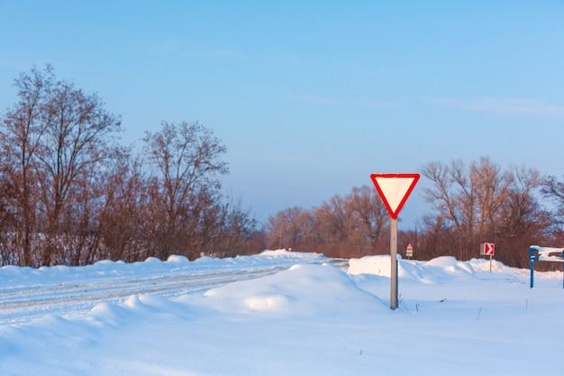 冬は道路の清掃が不十分です。雪が散らばって田舎の道。吹きだまりのある冬景色