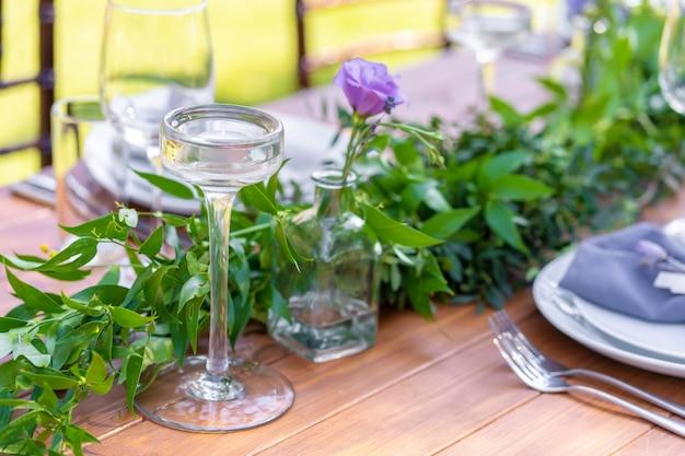 夏の屋外カフェで美しく装飾された木製テーブル。緑の枝と新鮮な花のテーブルデコレーション
