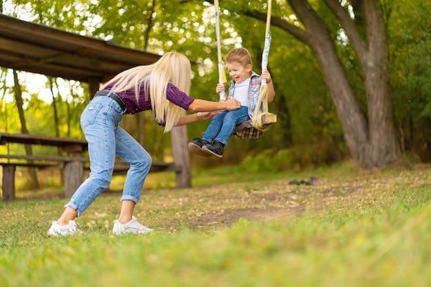 若いブロンドのお母さんは、緑豊かな公園のブランコで彼女の幼い息子を振る。幸せな子供時代。