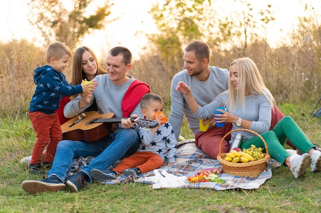 Путешествия, туризм, поход, пикник и люди концепции - группа счастливых друзей с палаткой и напитками, играя на гитаре в кемпинге