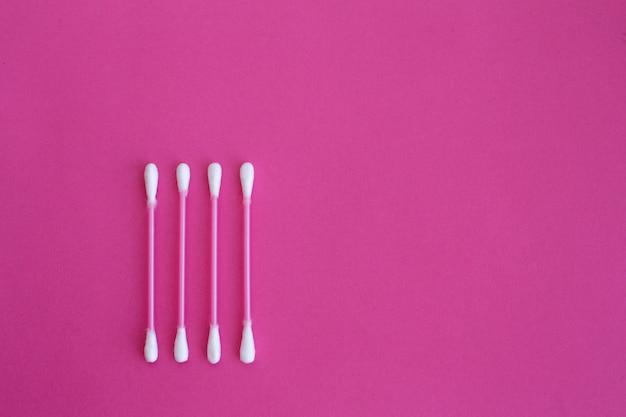 Четыре розовые ватные палочки с белыми головками, выложенные в вертикальной линии на розовом фоне