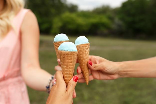 女性はアイスクリームコーンを手に保持します。