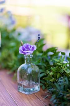 テーブルクロスのない木製テーブルが提供され、新鮮な花で飾られています