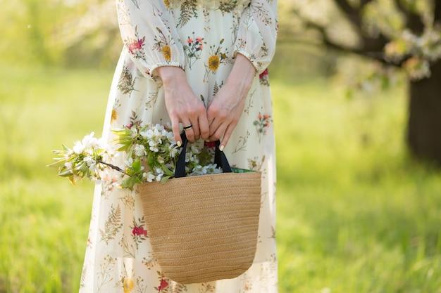 Женщина держит в руках стильную плетеную сумку с цветущими цветами в зеленом парке. весеннее романтическое настроение и красота природы