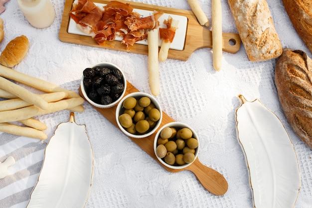 Еду выложите на плед для пикника. свежий белый хлеб, оливки и фотоаппарат лежали на белом одеяле
