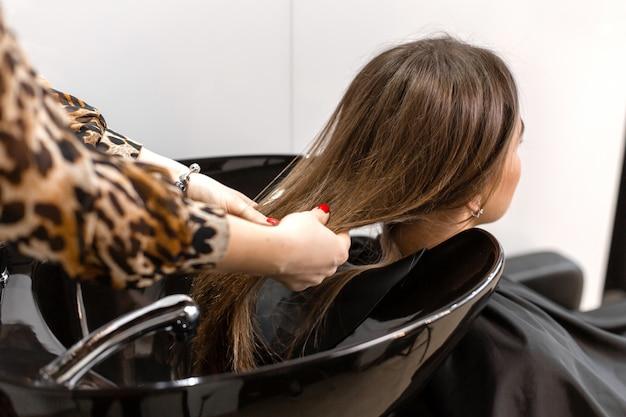 散髪マスターは彼女のクライアントの髪を洗います