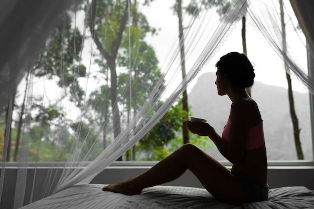 Девушка отдыхает и пьет чай в постели с видом на горы на острове шри-ланка