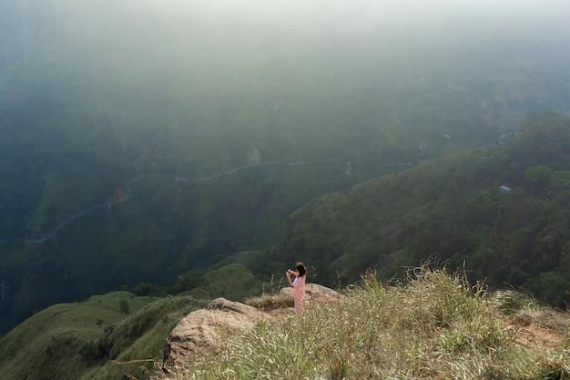 女の子は崖の上に立っている間山の景色を楽しんでいます