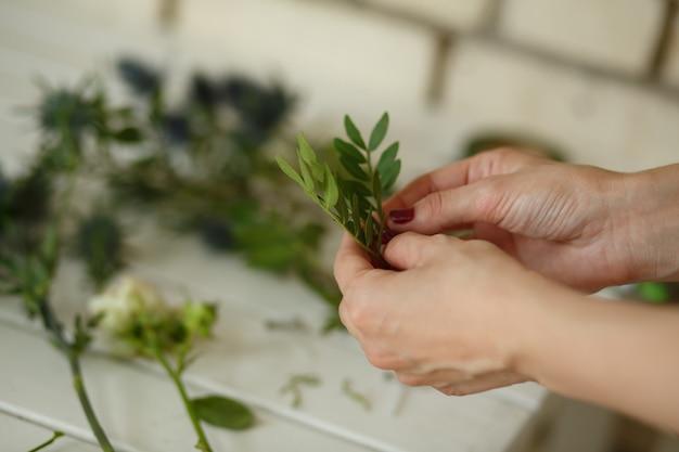 女性の花屋は結婚式の装飾のために新鮮な花からブーケを収集します