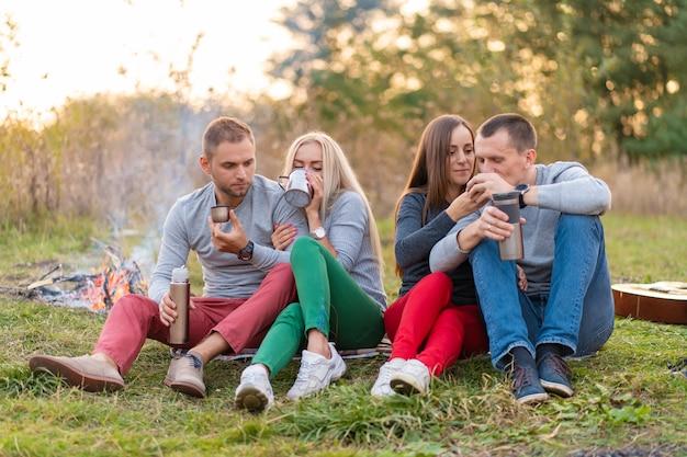 Группа друзей наслаждается согревающим напитком из термоса прохладным вечером у костра в лесу. весело провести время в поход с друзьями