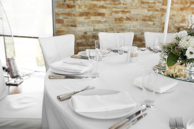 新鮮な花で飾られた結婚式のテーブルセッティング。白い皿、銀器、白いテーブルクロス