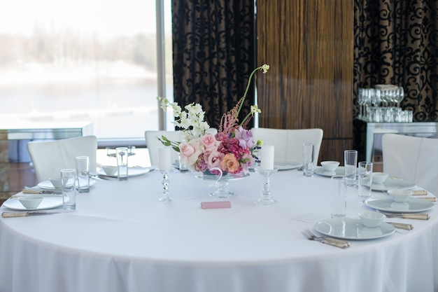 デリケートな生花で飾られたイベント用の白いレストランのテーブル