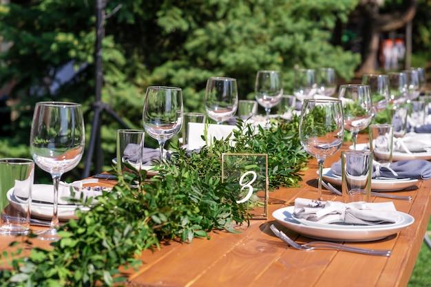 野外パーティーの準備。新鮮な花で飾られたテーブルを提供しています。テーブル番号。装飾の詳細
