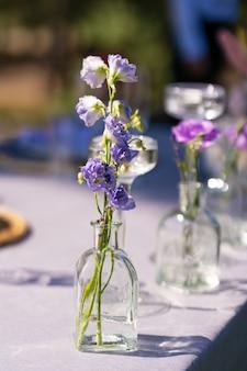 お祝いテーブルの装飾。ガラスの花瓶と新鮮な花。戸外での休日の装飾