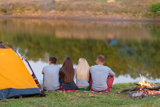 Группа друзей наслаждается видом, кемпинг с костром на берегу реки