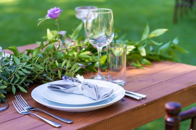 夏の屋外カフェで美しく装飾された木製テーブル。緑の枝と生花のテーブルデコレーション