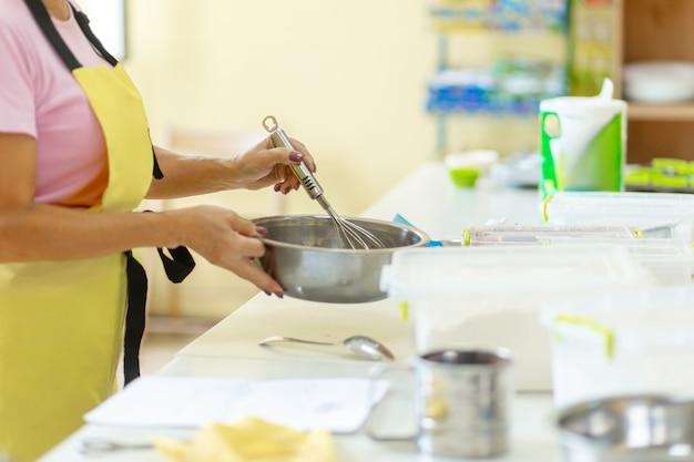 Женщина профессиональный кондитер готовит шоколадное тесто.