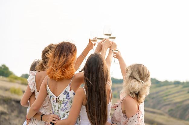 楽しんでいる女性の友人、乾杯、ワインを飲み、丘の風景のピクニックをお楽しみください。