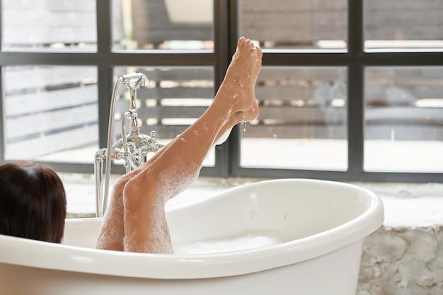 Великолепная женщина наслаждается в белой ванной, в светлой комнате с большим окном.