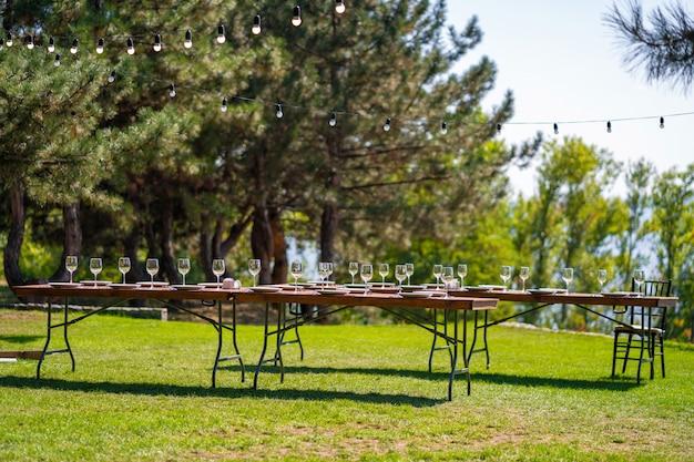 野外パーティーの準備。装飾されたテーブルがゲストを待っています。装飾の詳細