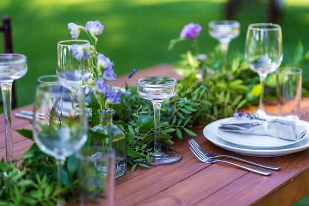 野外パーティーの準備。新鮮な花で飾られたテーブルを提供しています。テーブル番号。装飾の詳細。