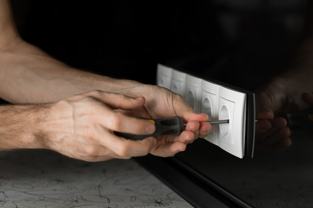 黒いガラスの壁に白いコンセントを分解するドライバーで電気技師の手のクローズアップ