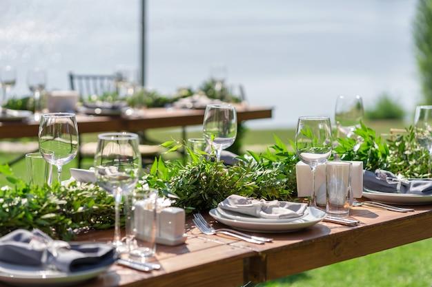 夏の屋外カフェで美しく装飾された木製のテーブル。緑の枝と生花のテーブルデコレーション。
