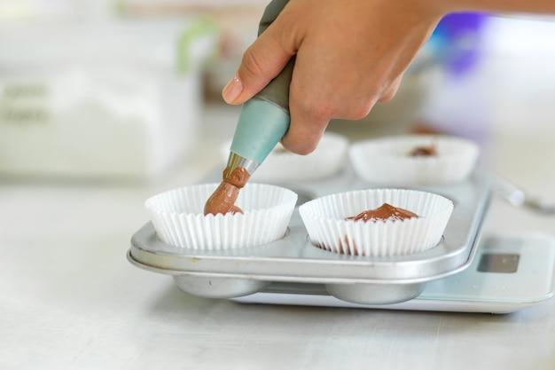 Женщина профессиональный кондитер выкладывает шоколадное тесто в форму для выпечки
