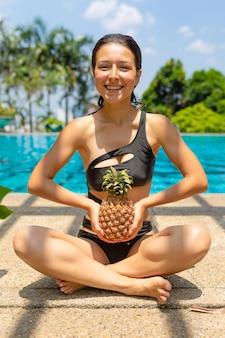 ジューシーなトロピカルフルーツがプールの端にクリスタルブルーの水で注がれています。贅沢な週末の休息