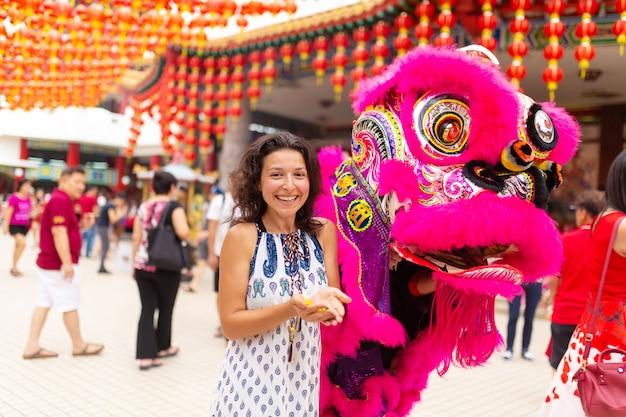 Китайский новый год в китайском храме. китайский дракон танцует и раздает сладости и мандарины. праздничное китайское развлечение