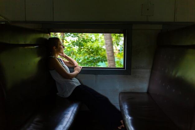 Поездка на поезде по шри-ланке. женщина сидит и смотрит в окно