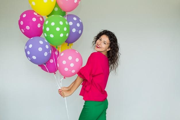 色の風船を持つ美しいかわいい陽気な女の子。