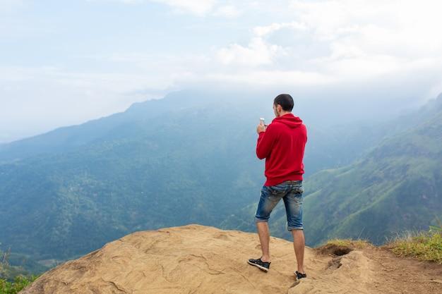 Человек, наслаждаясь горными пейзажами на краю обрыва
