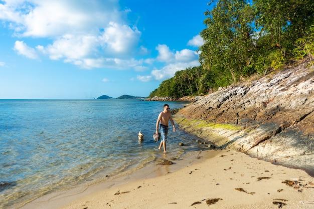 男と犬が海沿いの砂浜を歩いています。海沿いの熱帯の犬。
