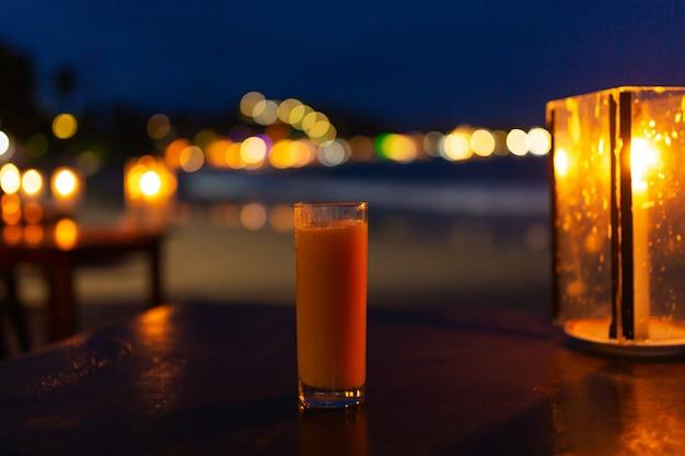 Стакан свежевыжатого сока вечером на пляже