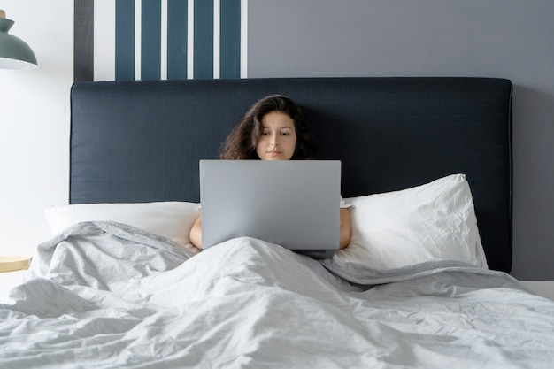 ノートパソコンが付いているベッドで美しいブルネットの少女。朝から深夜まで働きます。就寝前または朝の電子ガジェット。