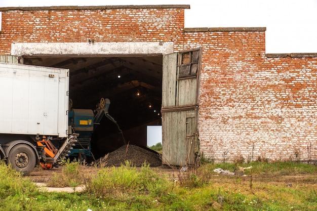 格納庫でヒマワリから種子を抽出する機械。ひまわりの種の山。ひまわりの収穫。